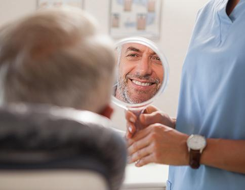 Man looking at smile with tooth-colored filling