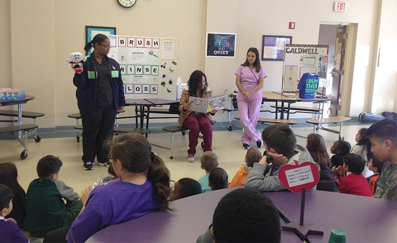 Three team members talking to kids about dental health