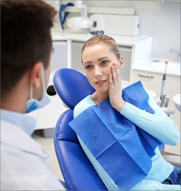 Woman holding cheek during emergency dentistry appointment