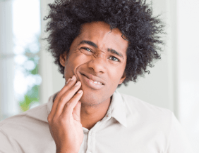 Man with toothache holding cheek