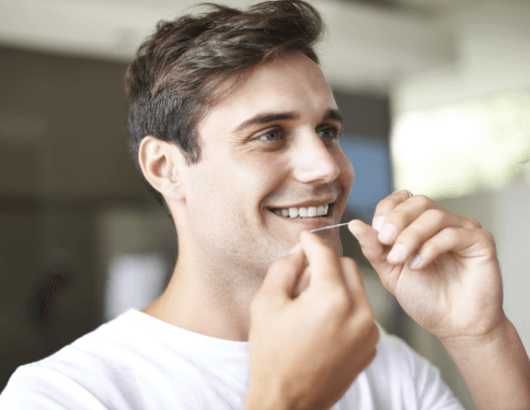 Man flossing teeth to prevent dental emergencies