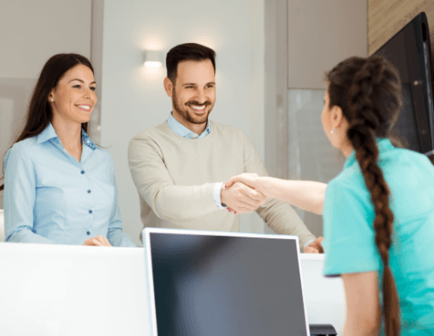 Man and woman checking in at dental office reception desk