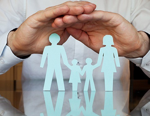 Hands covering paper cut out family