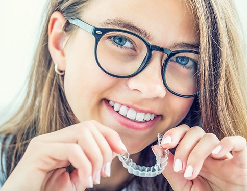 A young female wearing glasses and holding her clear Invisalign aligner in preparation for reinserting it in her mouth