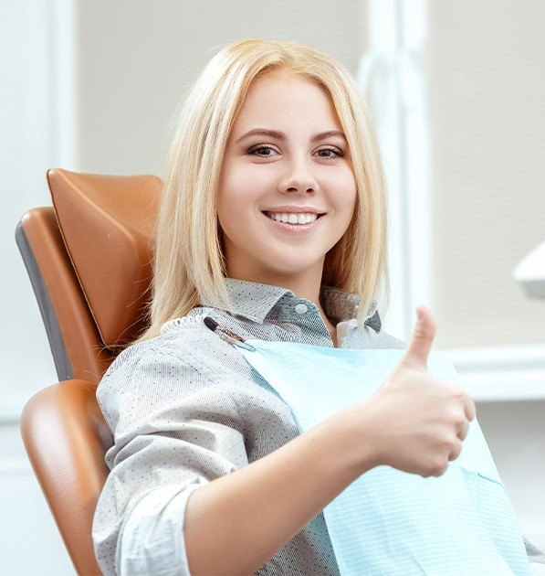 Woman in dental chair giving thumbs up after dentl checkup